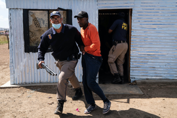 A metro policeman arrests a community member during an eviction in Lakeview Informal Settlement near Lawley, South of Johannesburg. Picture: James Oatway.